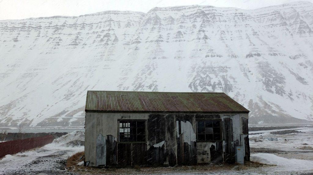 Proste szopy, schrony, magazyny, stały jeszcze w Ísafjörður nie wiadomo jakim prawem. Wyglądały jak domki z kart, trochę nawet jak obdarty do połowy ze skóry koza, a mimo wszystko trzymały się, dzielnie opierały sile natury. Warunki na które trafiłem z pewnością nie były jeszcze nawet połową tego co potrafi się tutaj dziać, a te cherlawe konstrukcje mimo wszystko wytrzymują pęd wiatru i grad. Stara quasi-szopa na tle smutnej góry za 66 równoleżnikiem - dla takich widoków również warto podróżować.